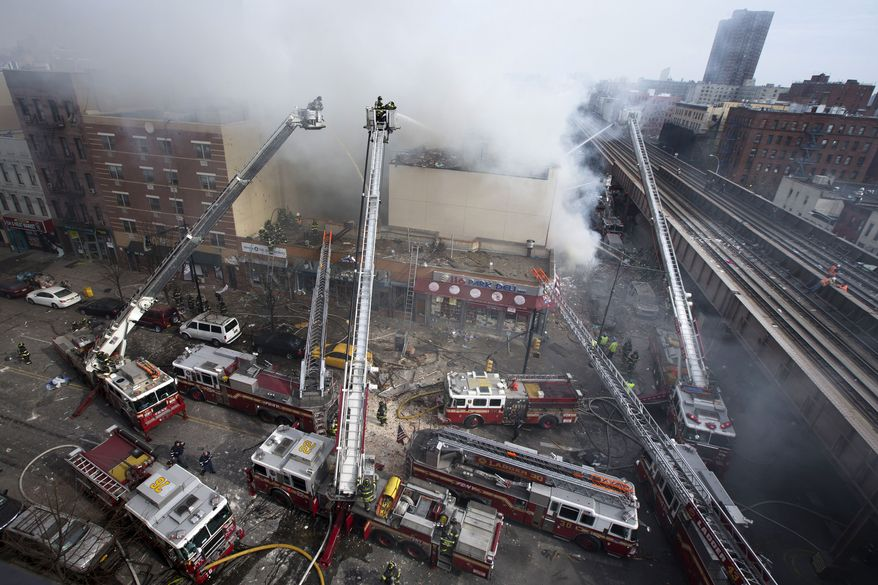 Firefighters battle a fire after a building collapse in the East Harlem neighborhood of New York, Wednesday, March 12, 2014 (AP Photo/John Minchillo)