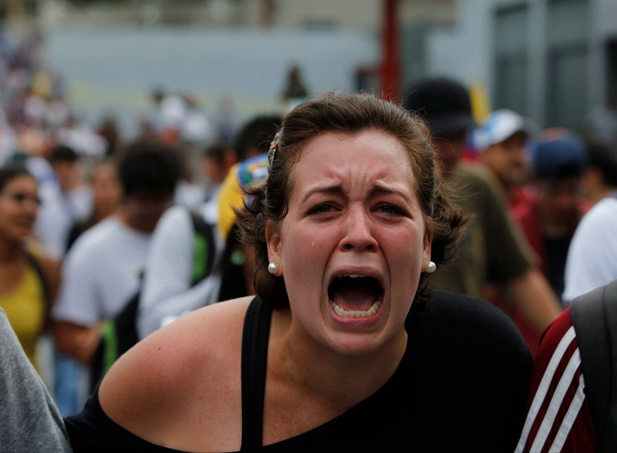 A student of Venezuela's Central University (UCV), shouts slogans against Venezuela's President Nicolas Maduro during a protest in Caracas, Venezuela, Wednesday, March 12, 2014.  According to local authorities, several deaths have been reported Wednesday, and a number of others, including National Guardsmen, have been wounded after being shot by unknown assailants in separate incidents in the central Venezuelan city of Valencia. (AP Photo/Fernando Llano)