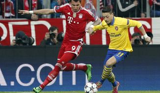 Bayern's Mario Mandzukic, left, and Arsenal's Mesut Ozil challenge for the ball during the Champions League round of 16 second leg soccer match between FC Bayern Munich and FC Arsenal in Munich, Germany, Tuesday, March 11, 2014. (AP Photo/Matthias Schrader)