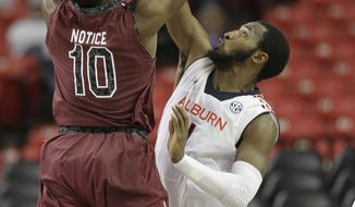 South Carolina Duane Notice (10) shoots against Auburn guard KT Harrell (1) during the second half in a first round Southeastern Conference tournament game, Wednesday, March 12, 2014, in Atlanta. (AP Photo/Steve Helber)