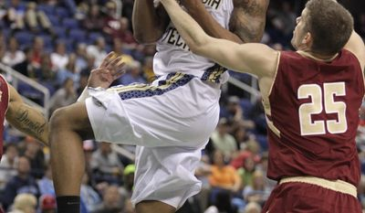 Georgia Tech's Marcus Georges-Hunt, left, drives past Boston College's Joe Rahon, right, during the second half of a first round NCAA college basketball game at the Atlantic Coast Conference tournament in Greensboro, N.C., Wednesday, March 12, 2014. (AP Photo/Bob Leverone)