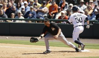Detroit Tigers' Bryan Holaday safely beats the throw to Miami Marlins first baseman Garrett Jones to allow Torii Hunter to score from third during the fourth inning of a spring exhibition baseball game in Lakeland, Fla., Thursday, March 13, 2014. (AP Photo/Carlos Osorio)