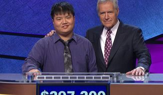 """This image released by Jeopardy Productions, Inc. shows host Alex Trebek with contestant Arthur Chu in front of a total of his winnings at a taping of """"Jeopardy,"""" in Culver City, Calif. Chu, who won big money while taking heat for his renegade style, has been defeated. Chu finished in third place with zero dollars on the Wednesday, March 12, 2014, edition of the syndicated quiz show. He had reigned for 12 days. His total winnings were $297,200. (AP Photo/Jeopardy Productions, Inc.)"""