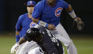 Seattle Mariners' Abraham Almonte is forced out at second as Chicago Cubs' Emilio Bonifacio watches his throw to first that completed complete a double play during the second inning of a spring exhibition baseball game Wednesday, March 12, 2014, in Peoria, Ariz. (AP Photo/Darron Cummings)