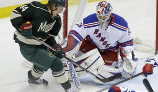 A scoring attempt by Minnesota Wild's Mikael Granlund, left, of Finland, is broken up as New York Rangers goalie Cam Talbot defends the net in the first period of an NHL hockey game on Thursday, March 13, 2014, in St. Paul, Minn. (AP Photo/Jim Mone)