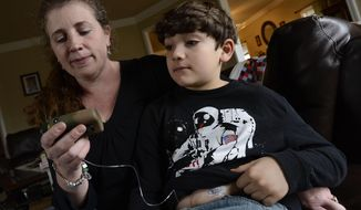 In this March 12, 2014 photo, Heidi Elbarky gives her son, Omar, 8, a dosage of insulin using his insulin pump at their home in Spring Hill, Tenn. The insulin pump feeds into a tube attached to Omar's body. Tennessee lawmakers are considering a bill that would add insulin to the list of medications school personnel can be trained to administer. (AP Photo/Mark Zaleski)