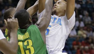 UCLA's Kyle Anderson pulls down a rebound against Oregon's Richard Amardi in the first half of an NCAA Pac-12 conference tournament quarterfinal college basketball game on Thursday, March 13, 2014, in Las Vegas. (AP Photo/Julie Jacobson)
