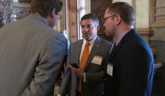 Kansas state Sen. Jake LaTurner, left, a Pittsburg Republican, talks to state GOP Chairman Kelly Arnold, center, and Heath Kohl, right, the state GOP's political director, during the Senate's debate on a bill making it harder for voters to switch parties before primary elections, Wednesday, March 12, 2014, at the Statehouse in Topeka, Kan. The state GOP backs the measure, which has gone to Republican Gov. Sam Brownback. (AP Photo/John Hanna)
