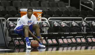 Kansas center Joel Embiid ties a shoe during practice for their opening NCAA basketball game in the Big 12 men's tournament in Kansas City, Mo., Wednesday, March 12, 2014. Kansas will play the winner of tonight's Texas Tech Oklahoma State game. (AP Photo/Orlin Wagner)