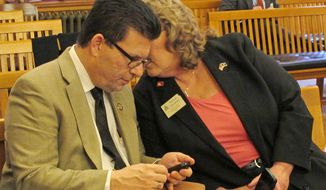 Kansas state Rep. Jim Howell, left, a Derby Republican, confers with Patricia Stoneking, right, the president of the Kansas State Rifle Committee, during a House committee debate on gun-rights legislation, Wednesday, March 12, 2014, at the Statehouse in Topeka, Kan. Howell is the main advocate of a bill stripping cities and counties of their power to regulate guns, and the measure has the support of Stoneking's group. (AP Photo/John Hanna)
