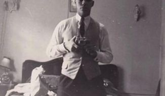 Colin Powell posted on Facebook a vintage snapshot of himself wearing a vest and holding a camera in front of a dresser mirror. (Colin Powell via Facebook)