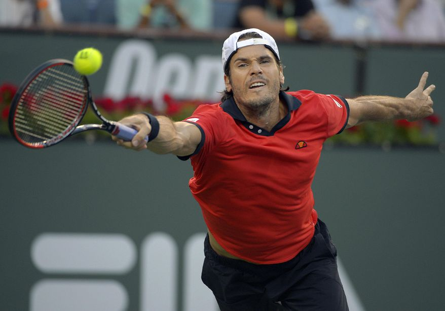 Tommy Haas, of Germany, reaches for the ball against Roger Federer, of Switzerland, during a fourth-round match at the BNP Paribas Open tennis tournament on Wednesday, March 12, 2014, in Indian Wells, Calif. (AP Photo/Mark J. Terrill)