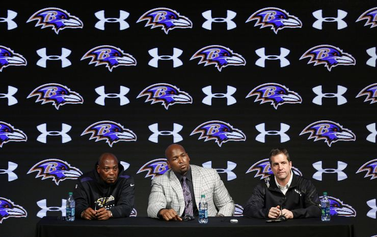 Baltimore Ravens tackle Eugene Monroe, center, sits between general manager Ozzie Newsome, left, and head coach John Harbaugh as he discusses his new five-year contract during an NFL football news conference, Wednesday, March 12, 2014, at the team's practice facility in Owings Mills, Md. (AP Photo/Patrick Semansky)