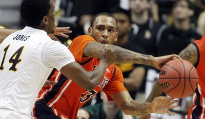 Cal State Fullerton guard Alex Harris, right, passes the ball around Long Beach State guard Branford Jones (14) in the first half of NCAA college basketball game in the Big West Conference men's ournament in Anaheim, Calif., Thursday, March 13, 2014.  (AP Photo/Alex Gallardo)