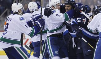 Vancouver Canucks' Shawn Matthias (27) holds back Winnipeg Jets' Dustin Byfuglien (33) from Canucks' Christopher Tanev (8) during the second period of an NHL hockey game Wednesday, March 12, 2014, in Winnipeg, Manitoba. (AP Photo/The Canadian Press, John Woods)