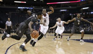 Central Florida guard Daiquan Walker, left, drives against Temple guard Will Cummings (2) during the first half of an NCAA college basketball game at the American Athletic Conference men's tournament Wednesday, March 12, 2014, in Memphis, Tenn. (AP Photo/Mark Humphrey)