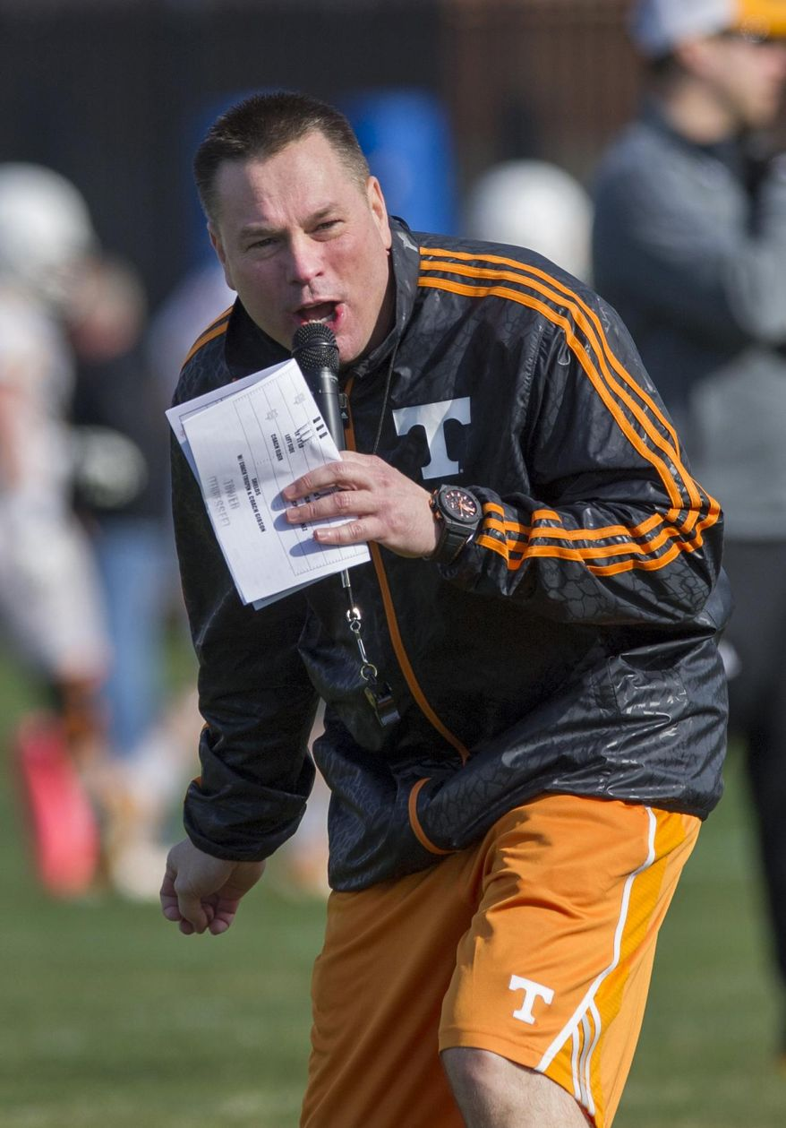 Tennessee head coach Butch Jones yells to his squad during spring practice Saturday, March 8, 2014, in Knoxville, Tenn. Jones has not set a timetable on when he will choose a starting quarterback. Jones said he'd decide on a starter whenever someone emerges as the clear-cut choice. (AP Photo/The Knoxville News Sentinel, Paul Efird)
