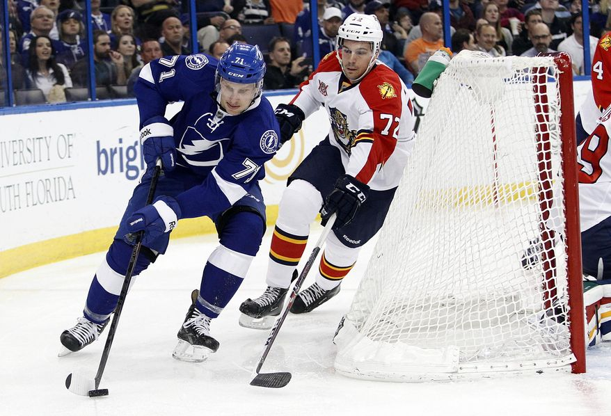 Tampa Bay Lightning right wing Richard Panik (71), of Slovakia, controls the puck behind the net against Florida Panthers defenseman Alex Petrovic (72) during the second period of an NHL hockey game Thursday, March 13, 2014, in Tampa, Fla. (AP Photo/Brian Blanco)