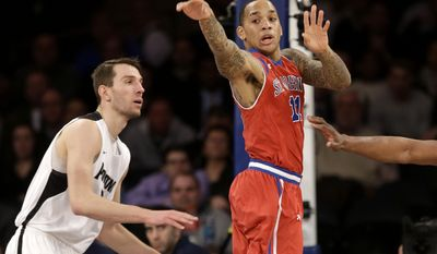 St. John's D'Angelo Harrison, right, passes the ball under the basket during the first half of an NCAA college basketball game against Providence in the quarterfinals of the Big East tournament at Madison Square Garden, Thursday, March 13, 2014, in New York. (AP Photo/Seth Wenig)