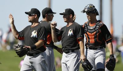 Miami Marlins third baseman Ty Wigginton, left, pitcher Sam Dyson, center, and catcher Kyle Skipworth celebrate their 4-2 win over the Detroit Tigers in a spring exhibition baseball game in Lakeland, Fla., Thursday, March 13, 2014. (AP Photo/Carlos Osorio)