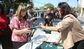 **FILE** Esther Guzman, left,  gets insurance information from Janelle Hartley, right, Thursday March 13, 2014, during a Covered California rally in Los Angeles. About 924,000 people have picked insurance plans through California's health care exchange as the race continues to attract more Latinos and younger people ahead of the enrollment deadline later this month.    (AP Photo/Nick Ut)
