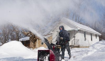 Robin Robinson, of Flint, snow blows his neighbors drive way, Wednesday, March 12, 2014, at Flint Southwestern High School in Flint, Mich. (AP Photo/MLive.com The Flint Journal, Katie McLean) LOCAL TV OUT; LOCAL INTERNET OUT.