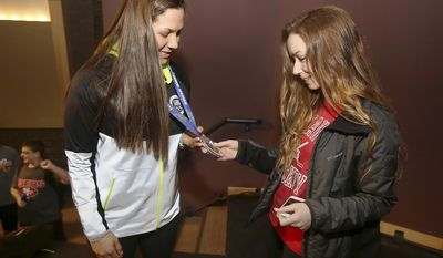 United States women's hockey player Megan Bozek, left, an Olympic silver medalists, shows her medal to senior Lora Khalfin as Bozek met with students and teachers Wednesday, March 12, 2014, at Stevenson High School in Lincolnshire, Ill. The former Stevenson graduate won the medal at the Sochi Winter Olympics. (AP Photo/Daily Herald, Gilbert R. Boucher II)  MANDATORY CREDIT, MAGS OUT