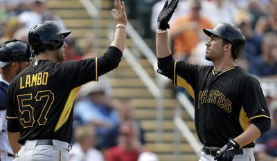 Pittsburgh Pirates first baseman Travis Ishikawa, right, is greeted by right fielder Andrew Lambo (57) after the two scored on Ishikawa's two-run homer in the sixth inning of an exhibition baseball game against the Minnesota Twins in Fort Myers, Fla., Wednesday, March 12, 2014. (AP Photo/Gerald Herbert)