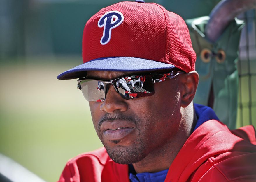Philadelphia Phillies Jimmy Rollins sits in the dugout after not playing for the third consecutive game during a spring exhibition baseball game against the New York Yankees in Clearwater, Fla., Thursday, March 13, 2014.  Rollins said the situation was unusual; that he is healthy, therefore he is not sure why Phillies manager Ryne Sandberg is not playing him. (AP Photo/Kathy Willens)