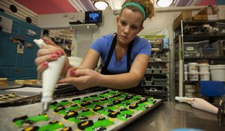 ADVANCE FOR USE SUNDAY, MARCH 16 AND THEREAFTER - In this Nov. 26, 2013 photo, Allison Mowry, of Mowry's Baking Co., frosts tractor shaped cookies at the bakery on Main Street in Decatur, Ill. The Mowry family, which has been perfecting its recipes and improving its techniques for many years, includes three generations of bakers. (AP Photo/Herald & Review, Danny Damiani)