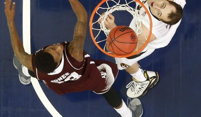 Missouri forward Ryan Rosburg (44) shoots over Texas A&M guard Jamal Jones (23) during the second half of an NCAA college basketball game in the second round of the Southeastern Conference men's tournament game, Thursday, March 13, 2014, in Atlanta. (AP Photo/John Bazemore)