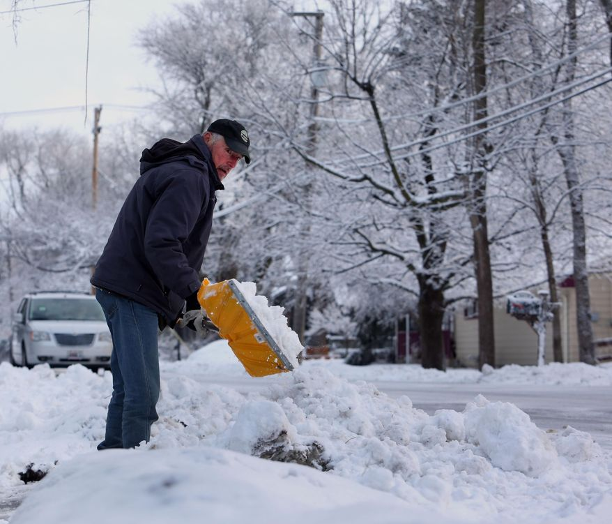 Jim Kleinwachter shovels snow out his driveway after a winter storm on Wednesday, March 12, 2014, in Warrenville, Ill. (AP Photo/Daily Herald, Bev Horne) MANDATORY CREDIT, MAGS OUT, TV OUT