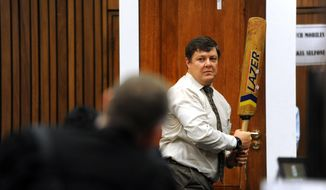 Forensic investigator Johannes Vermeulen, with a cricket bat in hand, demonstrates on a mock-up toilet cubicle, with the door, background, how the door could have been broken down with the bat, during the trial of Oscar Pistorius in court in Pretoria, South Africa, Wednesday, March 12, 2014. Pistorius is charged with the shooting death of  his girlfriend Reeva Steenkamp, on Valentines Day in 2013.  (AP Photo/Werner Beukes, Pool)
