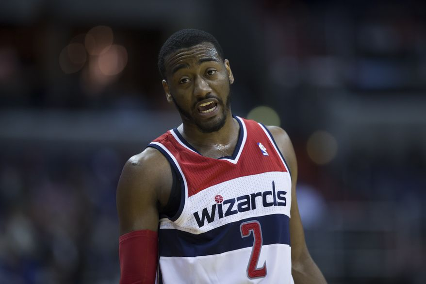 **FILE** Washington Wizards point guard John Wall (2) yells to teammates during the first half of an NBA basketball game against the Memphis Grizzlies on Monday, March 3, 2014, in Washington. (AP Photo/ Evan Vucci)