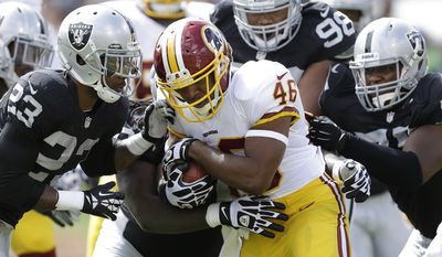 Washington Redskins running back Alfred Morris (46) is tackled by Oakland Raiders cornerback Tracy Porter (23), outside linebacker Kevin Burnett, rear, and defensive end Brian Sanford, right, during the first quarter of an NFL football game in Oakland, Calif., Sunday, Sept. 29, 2013. (AP Photo/Ben Margot)