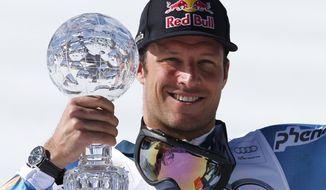 Norway's Aksel Lund Svindal shows the crystal globe trophy of the men's alpine skiing downhill at the World Cup finals in Lenzerheide, Switzerland, Wednesday, March 12, 2013. (AP Photo/Marco Trovati)