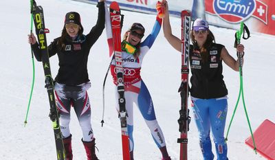 Switzerland Lara Gut, center, the winner, celebrates with second-placed Austria's Anna Fenninger, left, and third-placed  Slovenia's Tina Maze, after a women's alpine skiing Super-G at the World Cup finals in Lenzerheide, Switzerland, Thursday, March 13, 2014. (AP Photo/Marco Trovati)