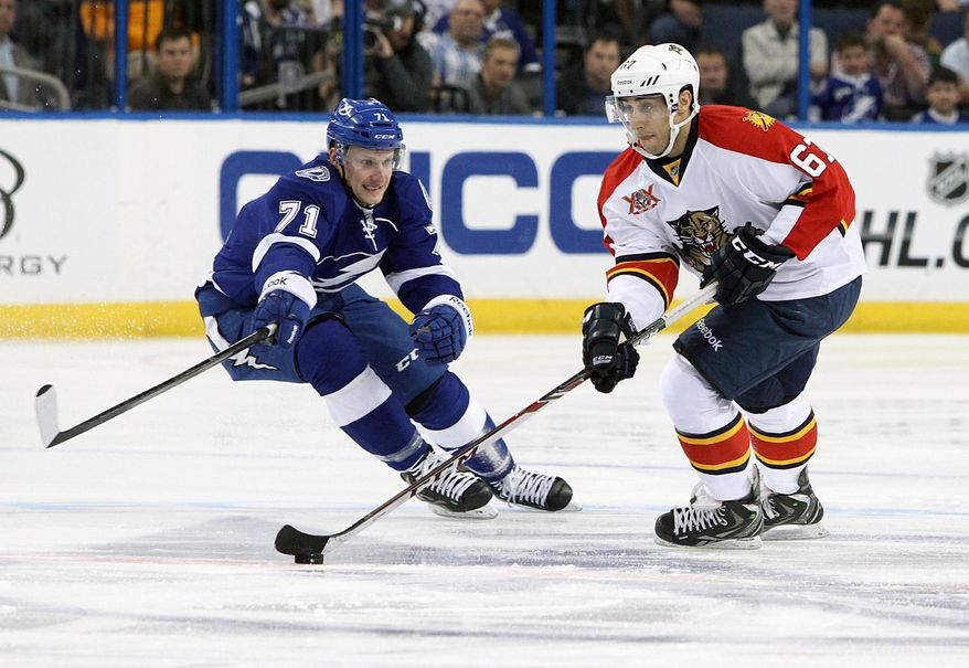 Florida Panthers center Vincent Trocheck (67) controls the puck against Tampa Bay Lightning right wing Richard Panik (71), of Slovakia, during the first period of an NHL hockey game Thursday, March 13, 2014, in Tampa, Fla. (AP Photo/Brian Blanco)