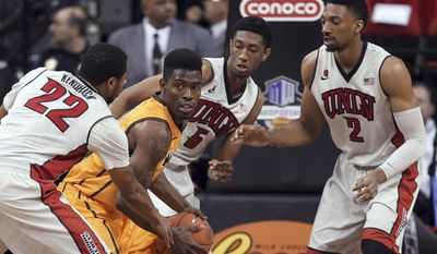 Wyoming's Derek Cooke Jr. looks to pass while surrounded by UNLV's Jelan Kendrick, left, Christian Wood and Khem Birch, right, during the first half of an NCAA college basketball game in the quarterfinals of the Mountain West Conference men's tournament Thursday, March 13, 2014, in Las Vegas. (AP Photo/Isaac Brekken)