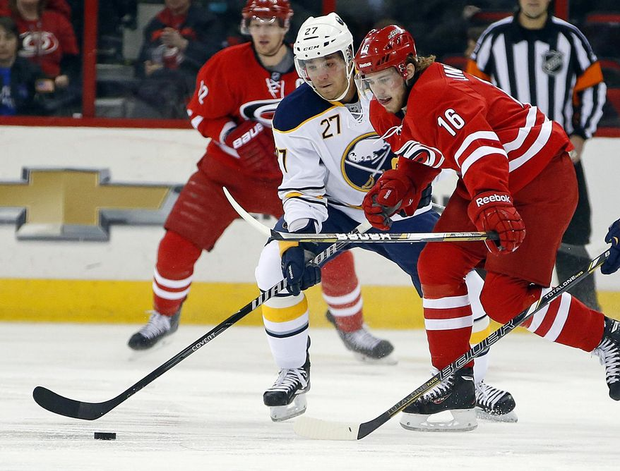 Carolina Hurricanes' Elias Lindholm (16), of Sweden, battles Buffalo Sabres' Matt D'Agostini (27) for the puck during the first period of an NHL hockey game in Raleigh, N.C., Thursday, March 13, 2014. (AP Photo/Karl B DeBlaker)