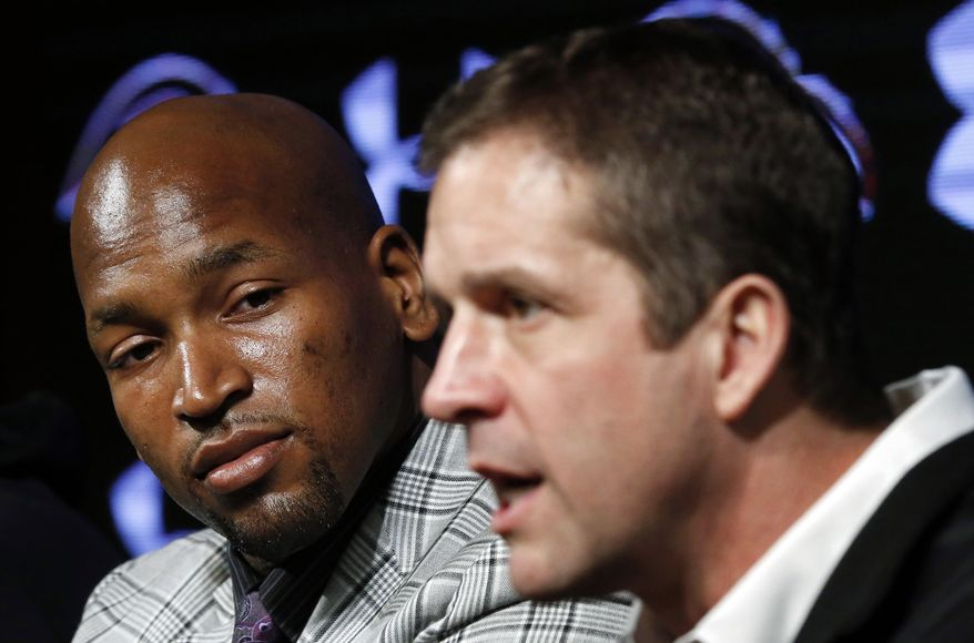 Baltimore Ravens tackle Eugene Monroe, left, listens as head coach John Harbaugh discusses Monroe's new five-year contract during an NFL football news conference, Wednesday, March 12, 2014, at the team's practice facility in Owings Mills, Md. (AP Photo/Patrick Semansky)