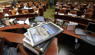 The House committee's final 200-plus page report of its investigation into former Attorney General John Swallow sits on the desk of House Speaker Rebecca Lockhart on the floor of the House of Representatives at the Utah State Capitol in Salt Lake City on Wednesday, March 12, 2014. The report that says Swallow traded favors with businessmen, obscured donations and destroyed records, among other allegations. (AP Photo/Rick Bowmer)