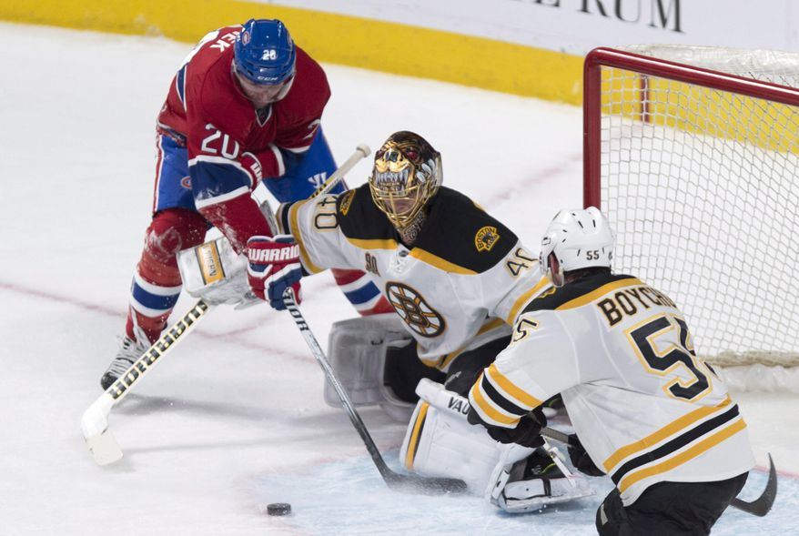 Boston Bruins goalie Tuukka Rask fends off Montreal Canadiens' Thomas Vanek as defenseman Johnny Boychuk looks on during second period NHL hockey action Wednesday, March 12, 2014 in Montreal. (AP Photo/The Canadian Press, Paul Chiasson)