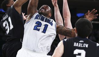 Seton Hall center Gene Teague (21) is blocked under the net by Butler forward Kameron Woods (31) as guard Alex Barlow (3) looks on during the first half of an NCAA men's college basketball game in the first round of the Big East tournament at Madison Square Garden, Wednesday, March 12, 2014, in New York. (AP Photo/John Minchillo)