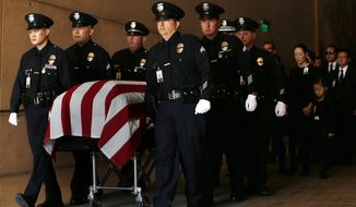 Pallbearers escort the casket of Los Angeles police officer Nicholas Lee before funeral services at the Cathedral of Our Lady of the Angels on Thursday, March 13, 2014 in Los Angeles.  Lee, 40, a Los Angeles police officer, was killed last week in a collision between a patrol car and a truck in Beverly Hills. His partner, a rookie just a few months out of the academy, was hospitalized and later released. The truck driver also was injured. The collision occurred as the officers were responding to a trouble call. The crash remains under investigation. Lee leaves a wife and two young daughters.  (AP Photo/Los Angeles Times, Robert Gauthier, Pool)