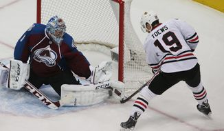 Colorado Avalanche goalie Semyon Varlamov, left, of Russia, makes a pad save of a shot off the stick of Chicago Blackhawks center Jonathan Toews in the first period of an NHL hockey game in Denver on Wednesday, March 12, 2014. (AP Photo/David Zalubowski)