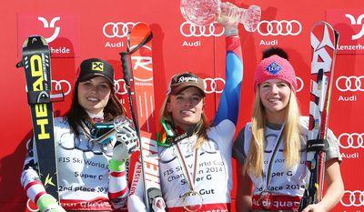 Switzerland Lara Gut, center, the winner, celebrates with second-placed Austria's Anna Fenninger, left, and third-placed  Liechtenstein' s Tina Weirather, after a women's alpine skiing Super-G at the World Cup finals in Lenzerheide, Switzerland, Thursday, March 13, 2014. (AP Photo/Marco Trovati)