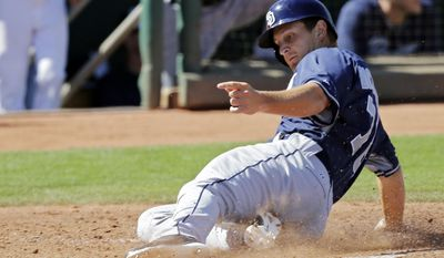San Diego Padres' Alex Dickerson slides home to score on a single by Alex Castellanos in the fourth inning of a spring exhibition baseball game against the Cleveland Indians, Wednesday, March 12, 2014, in Goodyear, Ariz. (AP Photo/Mark Duncan)