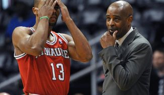 Milwaukee Bucks coach Larry Drew, right, calls in a play to Ramon Sessions (13) in the first half of an NBA basketball game against the Atlanta Hawks on Thursday, March 13, 2014, in Atlanta. (AP Photo/David Tulis)