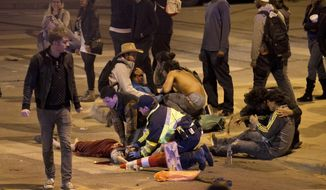 People are treated after being struck by a vehicle on Red River Street in downtown Austin, Texas, during SXSW on Wednesday March 12, 2014. Police say two people were confirmed dead at the scene after a car drove through temporary barricades set up for the South By Southwest festival and struck a crowd of pedestrians.  (AP Photo/Austin American-Statesman, Jay Janner)